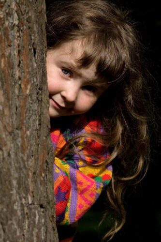 Young child peeking from behind tree