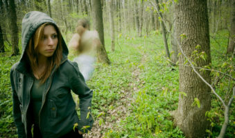 Young woman walking through woods