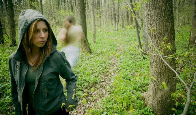 Young woman walking through woods