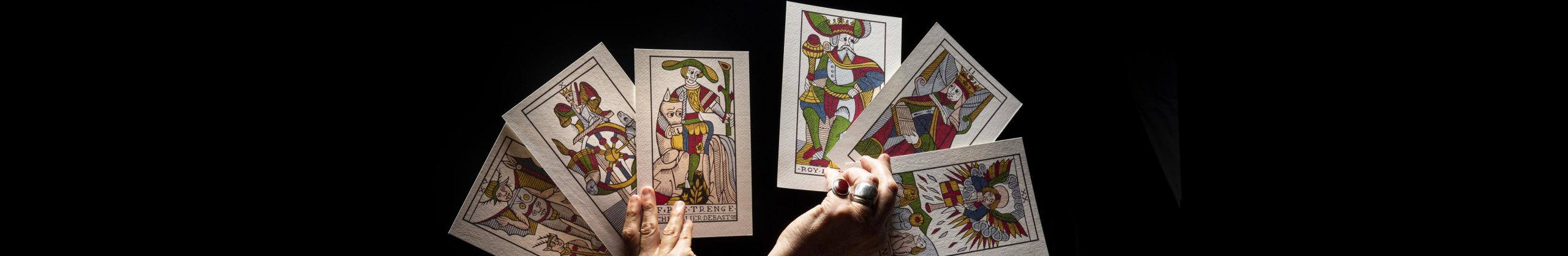 Six tarot cards held in two hands against dark background.